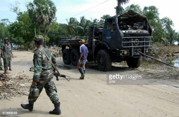 Sri Lankan soldiers survey tsunami damage to their camp in the eastern coastal district of Batticaloa 28 December 2004 The tsunami which struck Sri...