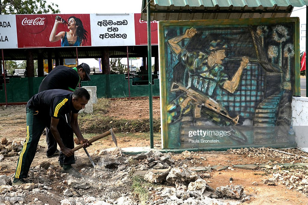 Sri Lankan soldiers work long the road at site of a war memorial, in Elephant Pass, July 9, 2013. War's end has unleashed Sinhalese nationalism that has Tamils fearful of ethnic cleansing. They number around 15 per cent of the 21 million population. Sri Lanka's main Tamil party has won the first elections in the island's north after decades of ethnic war. After votes were counted, results show that the Tamil National Alliance (TNA) won 30 seats out of the 38 member council following Northern Provincial Council elections with President Mahinda Rajapaksa's coalition winning seven of the other seats.