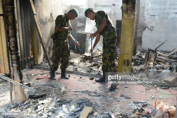 Sri Lankan Special Task Force soldiers sift through the debris in the compound of a home in Salawa on the edge of the capital Colombo on June 6 hours...