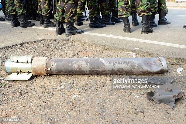 Sri Lankan Special Task Force soldiers stand near a mortar bomb in the compound of a home in Salawa on the edge of the capital Colombo on June 6...