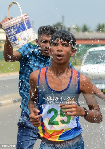 Sri Lankan spectators pour water onto a competitor during a road race held in Piliyandala near Colombo on April 14 as part of traditional festival...