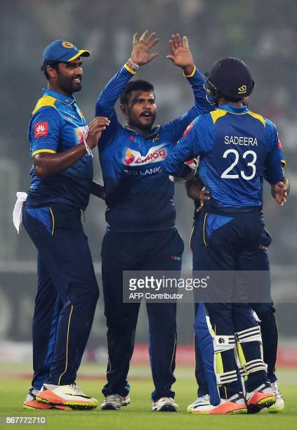 Sri Lankan spinner Dilshan Munaweera celebrates with teammates after taking the wicket of Pakistani batsman Fakhar Zaman during the third and final...