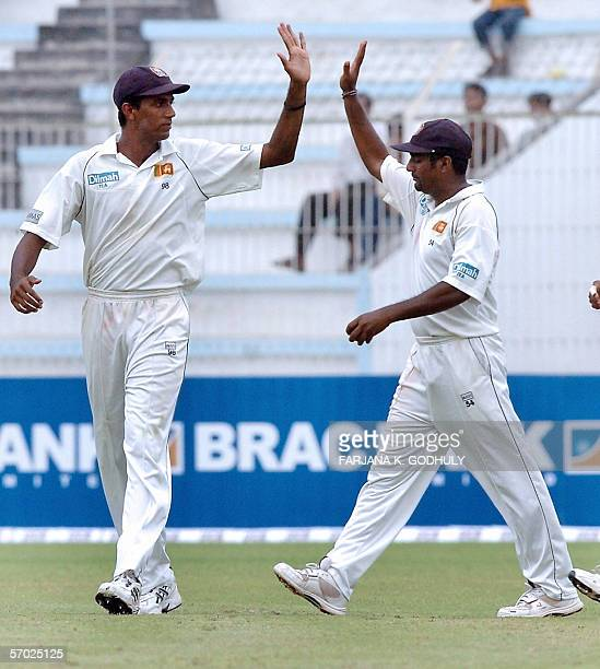 Sri Lankan spinner Muttiah Muralitharan celebrates with his teammate Farveez Maharoof the dismissal of Bangladeshi batsman Mohammad Rafiq during the...