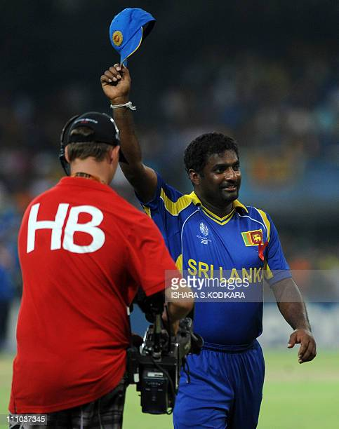 Sri Lankan spinner Muttiah Muralitharan waves at spectators as he walks back to the dressing room during the World Cup semi-final game against New...