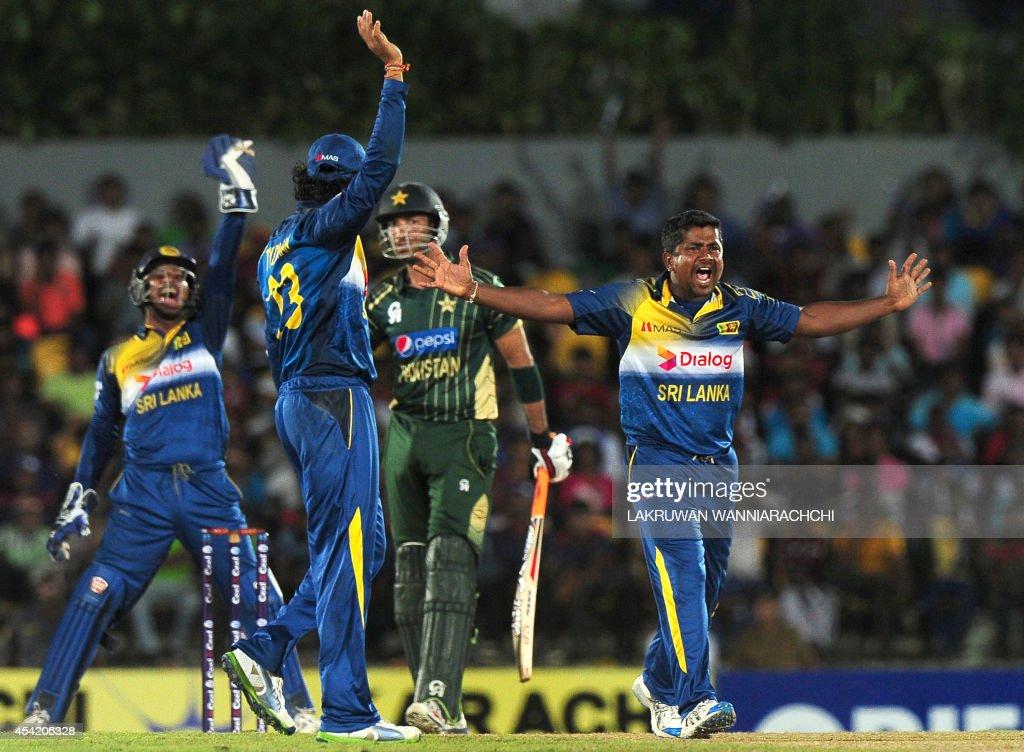 Sri Lankan spinner Rangana Herath (R) successfully appeals for a Leg Before Wicket (LBW) decision against Pakistan batsman Sohaib Maqsood (C) during the second One Day International (ODI) match between Sri Lanka and Pakistan at the Suriyawewa Mahinda Rajapakse International Cricket Stadium in the southern district of Hambantota on August 26, 2014.