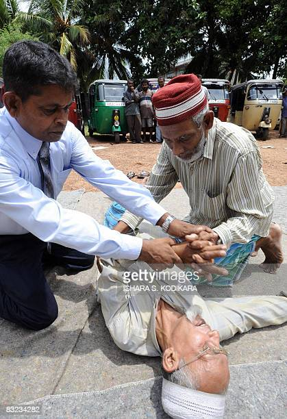A Sri Lankan St John Ambulance trainer helps a tuk tuk driver to apply aid during a first aid programme to teach basic life saving skills in Colombo...