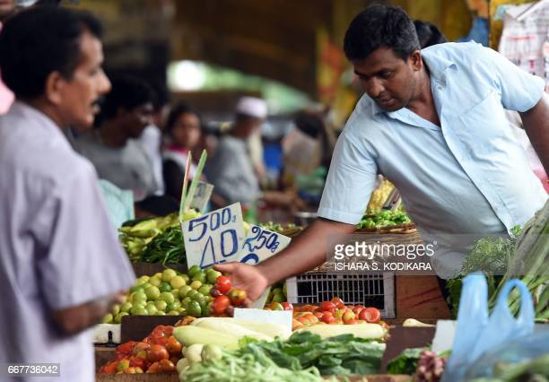 Sri Lankan stallholder arranges tomatoes at a market in Colombo on April 12 ahead of the traditional Sinhala and Tamil New Year Sri Lanka marks the...