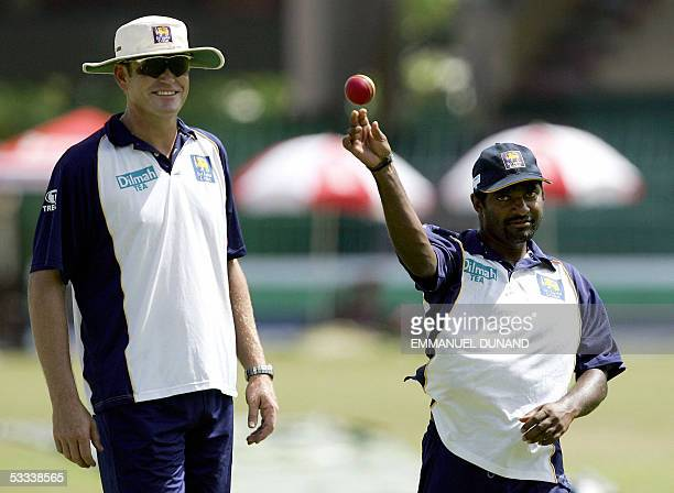 Sri Lankan star offspinner Muttiah Muralitharan throws the ball while coach Tom Moody looks on during training in Colombo 08 August 2005 Sri Lanka...