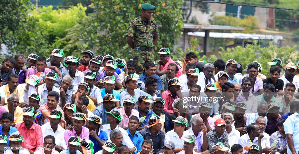 A Sri Lankan STF Police officer looks on at Sri Lankan tea plantation workers of Indian origin during a rally attended by Indian PM Narendra Modi in Norwood, about 140 kilometers (87.5 miles) east of Colombo, Sri Lanka, Friday, May 12, 2017