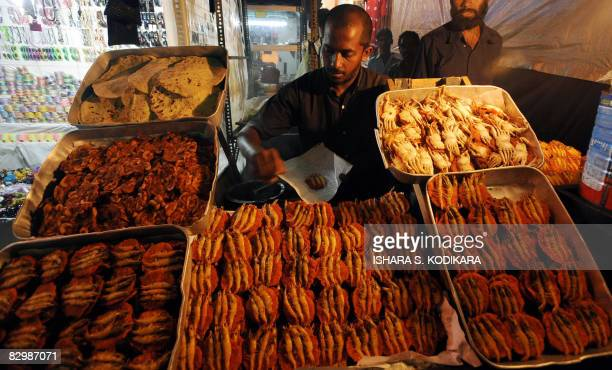 A Sri Lankan street vendor displays food at a night market in Colombo's Pettah area on September 24 2008 The market comes alive during the fasting...