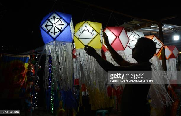 A Sri Lankan street vendor hangs lanterns for sale ahead of the Vesak Festival in Colombo on May 4 2017 Sri Lankan Buddhists are preparing to...