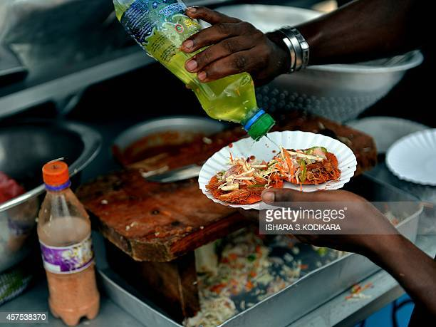 A Sri Lankan street vendor prepares prawn snacks at the Galle Face Beach in Colombo on October 20 2014 AFP PHOTO/ Ishara S KODIKARA