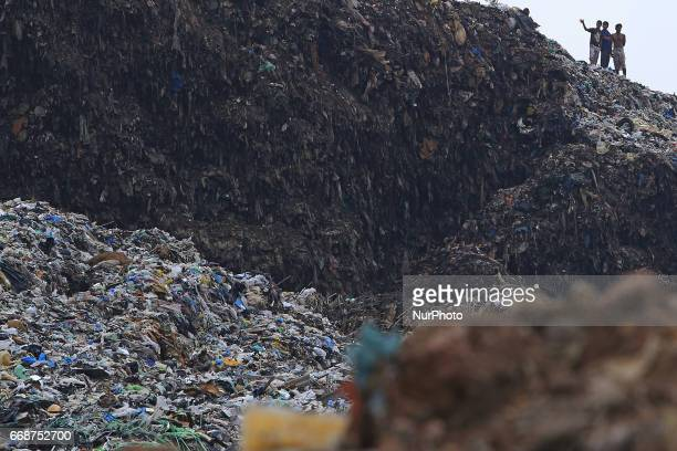 Sri Lankan survivors look on from on top of a collapsed garbage mountain in Colombo Sri Lanka 15 April 2017 A large section of garbage dump collapsed...
