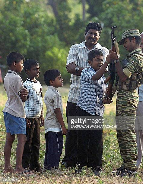 WITH SRI LANKAUNRESTTIGERSTRAINING A Sri Lankan Tamil Tiger guerrilla shows an automatic gun to Tamil children during a selfdefence training in the...