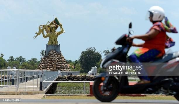 A Sri Lankan Tamil woman rides a motorbike past a memorial dedicated to the Sri Lankan Army in the northern district of Mullaittivu on May 17 ahead...