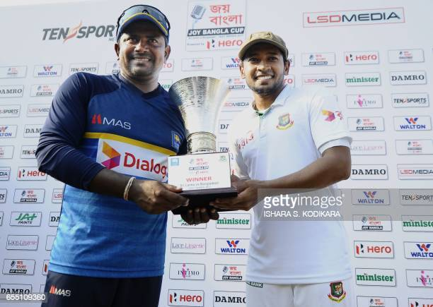 Sri Lankan Test captain Rangana Herath and Bangladesh Test captain Mushfiqur Rahim pose for photographers with the series trophy after Bangladesh's...