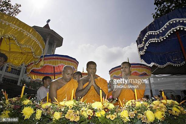 Sri Lankan Theravada Buddhist monks pay their respects as they place candles in front of a statue of Buddha at the conclusion of a multifaith prayer...