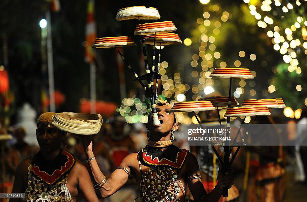 Sri Lankan traditional dancers perform in front of the Gangarama Temple during the Navam Perahera festival in Colombo on February 3, 2015. Monks, drummers, dancers and some 50 trained elephants, mostly from entral part of the island, thronged into Colombo from various regions of Sri Lanka to participate in the city's biggest two day annual Buddhist procession starting February 2.