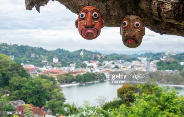 sri lankan traditional fire devil masks to sell at a store near the road, with kandy lake on the background - indigenous culture stock pictures, royalty-free photos & images