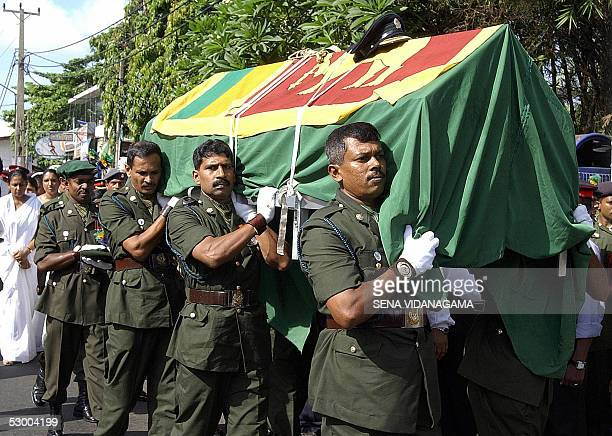 Sri Lankan troops carry the coffin of slain army intelligence officer Major Nizam Mutalif which is draped with the national flag in the Dehiwala...