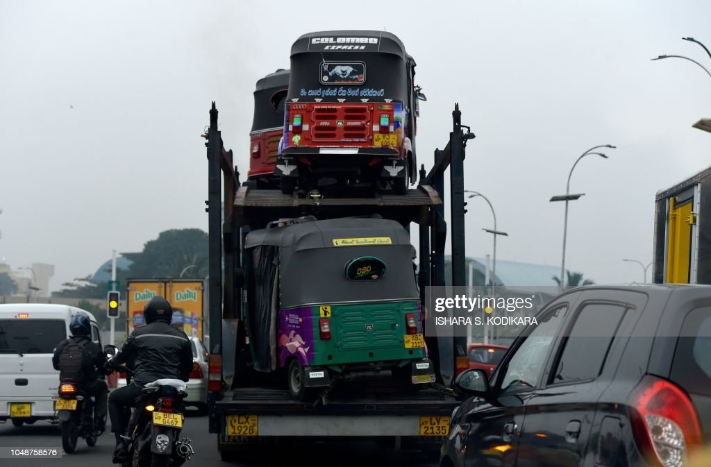 A Sri Lankan truck transport three-wheeler auto rickshaw along a