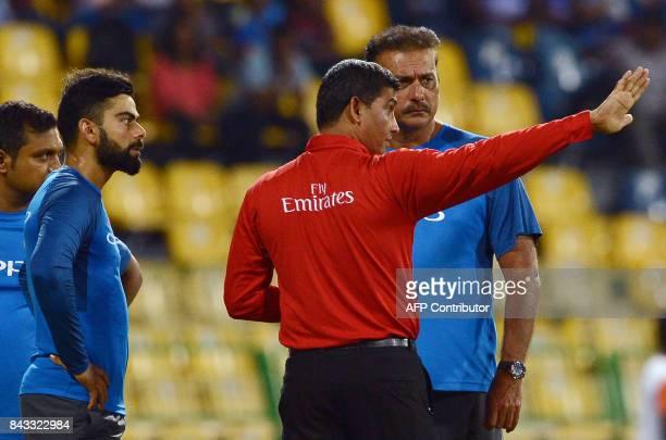 Sri Lankan umpire Ruchira Palliyaguruge speaks with Indian captain Virat Kohli and coach Ravi Shastri at the R Premadasa Stadium after rain delayed...