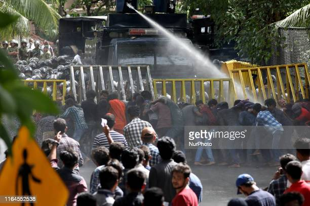 Sri Lankan university students attempt to topple police barricades as police fire water cannon during a protest march in Colombo on August 28, 2019....
