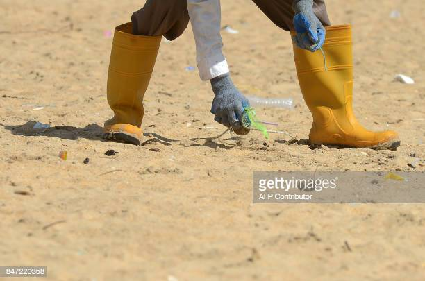 A Sri Lankan urban development staff takes part in a beach cleanup effort on September 15 2017 at Mount Lavinia on the outskirts of the capital...