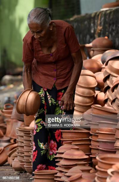 A Sri Lankan vendor sorts clay pots as she waits for customers at a roadside stall in Colombo on April 12 ahead of events to mark the traditional...