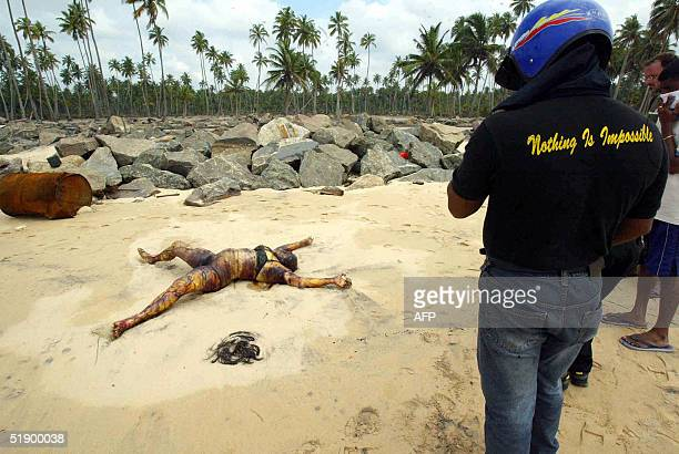 Sri Lankan villagers look at a body lying on a beach after tidal waves crashed onto land in Sinigame near the tourist town of Hikaduwa on the...
