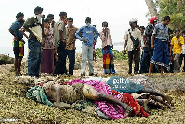 Sri Lankan villagers look at dead bodies piled up together after they were taken out from train carriages which were swept away by tidal waves in...