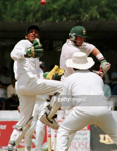 Sri Lankan wicket keeper Kumar Sangakkara attempts to hold the ball as South African batsman Jonty Rodes looks on during the fourth day of the first...