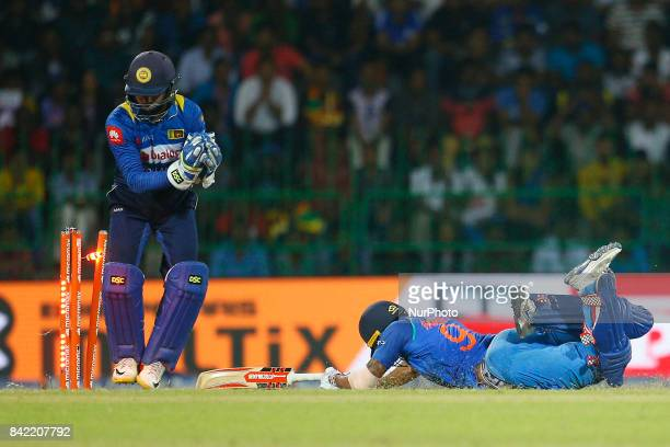 Sri Lankan wicket keeper Niroshan Dickwella removes the bails as Indian cricketer Manish Pandey dives in to survive a run out during the 5th and...