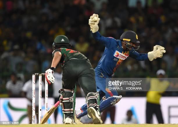 Sri Lankan wicketkeeper Kusal Perera celebrates taking a catch to dismiss Bangladesh cricketer Tamim Iqbal during the sixth Twenty20 international...