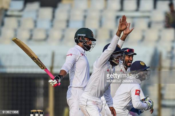 Sri Lankan wicketkeeper Niroshan Dickwella celebrates with his teammate after the dismissal of Bangladeshi cricketer Tamim Iqbal during the fourth...