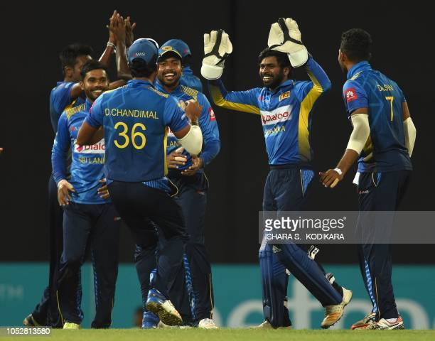 Sri Lankan wicketkeeper Niroshan Dickwella celebrates with teammates after he dismissed England cricketer Jos Buttler during the fifth and final one...