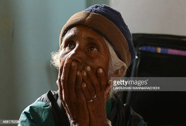 A Sri Lankan woman affected by a landslide look up as she sits at a governmentrun relief camp at Poonagalla on October 31 2014 The military deployed...