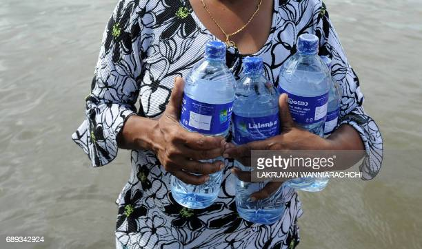 A Sri Lankan woman carries bottles of water through floodwaters in Dodangoda village in Kalutara on May 28 2017 Emergency teams rushed to distribute...