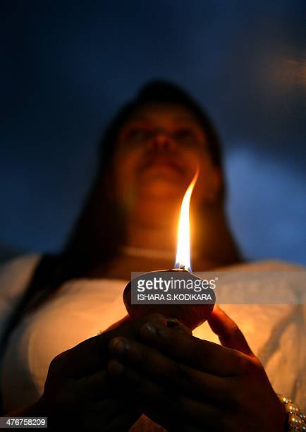 A Sri Lankan woman holds a coconut oil lamp at Colombos commercial area of Maradana to mark the 16th anniversary of a bus bombing that killed at...