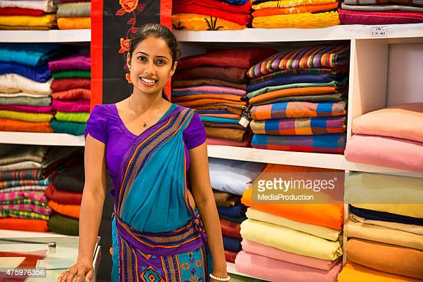 sri lankan woman in a sari as a shop assistant - indian woman stock photos and pictures