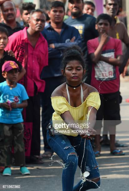 A Sri Lankan woman participates in a traditional 'Catch the Egg Toss' game in a field during Sinhala and Tamil New Year celebrations in Colombo on...