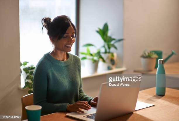 sri lankan woman smiling with green jumper working on laptop at home. - sustainable lifestyle stock pictures, royalty-free photos & images