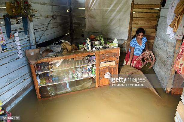 Sri Lankan woman wades through floodwaters inside her home in Kelaniya suburb of the capital Colombo on May 18 2016 Rescue workers on May 18...