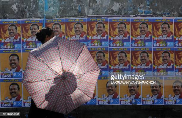 Sri Lankan woman walks past election posters of President Mahinda Rajapaksa in the Colombo suburb of Piliyandala on January 6, 2015. Rajapaksa will...