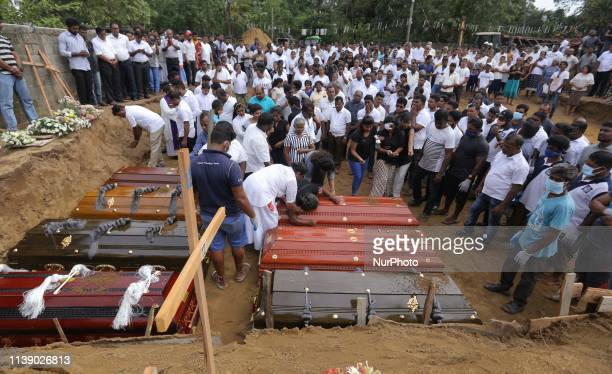 A Sri Lankan woman weeps as Coffins are laid for burial as a Sri Lankan catholic priest surrounded by devotees and family members of the victims...