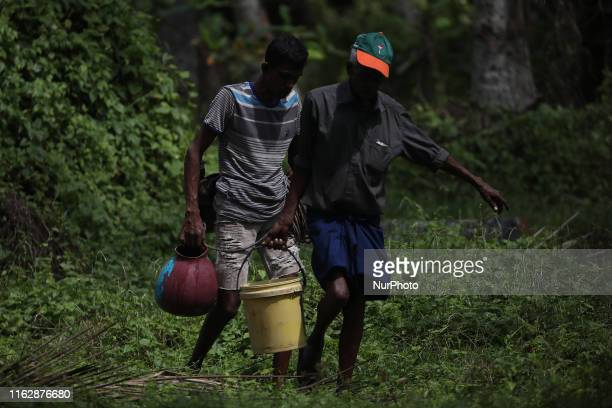 Sri Lankan worker Donald Perera and toddy tapper Niroshan Thilakarathne carry pots after collecting sap from a coconut tree in Wadduwa about 50...