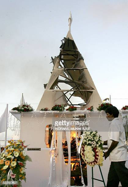 Sri Lankan worker places flowers in front of the burning funeral pyre of slain Sri Lankan Foreign Miinister Lakshman Kadirgamar in Colombo15 August...