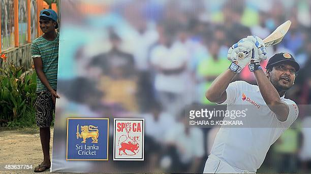 Sri Lankan workers carry a billboard bearing the image of Sri Lanka cricketer Kumar Sangakkara at the Galle International Cricket Stadium in Galle on...