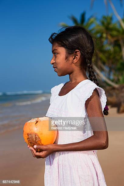 Sri Lankan young girl holding coconut on a beach, Ceylon