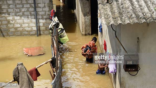 Sri Lankan youths wade through floodwaters as they go about their daily chores in Kelaniya suburb of the capital Colombo on May 18 2016 Rescue...